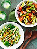 A carrot and mange tout salad and a tomato and cucumber salad