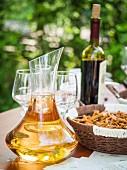 Georgischer Kvevri-Weisswein zur Degustation in Dekantierkaraffe auf Tisch im Freien