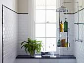 An Glas Trennscheibe gehängtes Regal mit Duschutensilien, Ablage aus schwarzem Stein vor Sprossenfenster und weiss geflieste Wänden