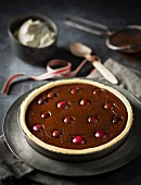 A chocolate tart with cherries