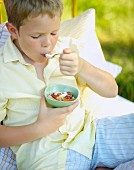 A boy eating muesli for breakfast in bed in a field