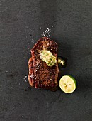 Peppered beefsteak with herb butter (seen from above)