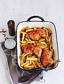 Chilli chicken with chips in a baking dish