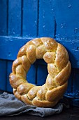 A brioche wreath leaning against a blue wooden door