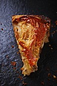 A slice of apple cake on a slate platter