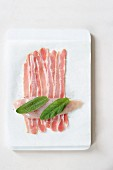 A raw chickens breast with sage leaves on bacon rashers