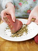 Tuna fish steak being coated in peppercorns
