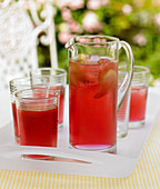 Berry juice with lines and ice cubes in a jug and in glasses