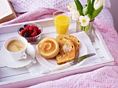 A breakfast tray with a cup of coffee, bread and toast, berries and fresh flowers