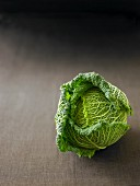 A Savoy cabbage on a grey surface