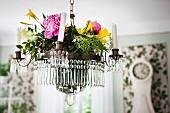 Sommerblumen auf Kerzenleuchter mit Glasschmuck und weissen Kerzen, von Decke abgehängt