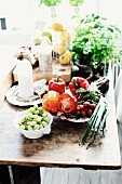 Dishes of fruit and vegetables and pots of herbs on rustic wooden table