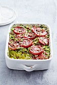Potato cake in a baking dish with tomato and courgette