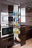 Hochglänzende Edelholzfronten in zeitgenössischer Küche; Apothekerschank mit Fächern für Vorratshaltung neben integrierten Edelstahlbacköfen