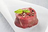Raw beef fillet wiht peppercorns and basil leaves