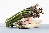 Bunches of asparagus, one lying on the other