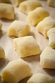 Freshly made, uncooked potato gnocchi on baking paper