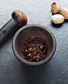 Clove in a mortar with a pester and nutmegs next to it