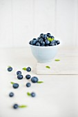 Fresh blueberries in a white bowl and in front of it