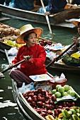 Thailändische Marktfrau auf schwimmendem Gemüsestand