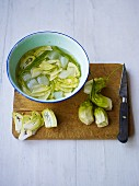 Puntarelle hearts (Italian chicory) on a chopping board, sliced and in a bowl of iced water
