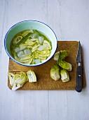 Puntarelle-Herzen (italienische Salatsorte, Zichorienart) auf Schneidebrett, geschnitten und in Schüssel mit Eiswasser
