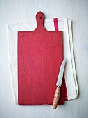 A red wooden chopping board and a knife on a tea towel