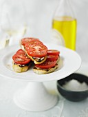 Grilled bread topped with sliced tomatoes and olive oil on a cake stand