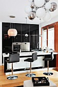 A black and white designer kitchen with shiny cupboards, leather stools at the breakfast bar and various round lamps