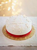 A festive Christmas cake decorated with a red satin ribbon
