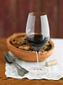 A glass of red wine with tapas in a terracotta bowl in the background