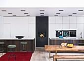 Rustikaler Holztisch mit Bank vor offener Küche, seitlich filigrane Barhocker im Retro Stil vor monolithischer Theke und weisser Einbauschrank