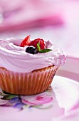 A cupcake topped with strawberry cream and fresh berries