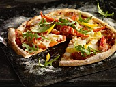 A pepper, rocket and peperoni pizza on an old baking try