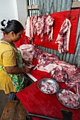 A woman selling meat at a market in Cha Am, Thailand