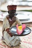 Kleine Keramikfigur mit duftenden Blütenblättern
