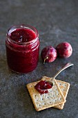 Plum jam in a jar and on a spoon with crackers