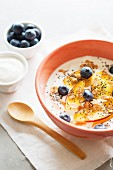 Yoghurt with peaches, blueberries, whole-grain flakes and chia seeds in a muesli bowl