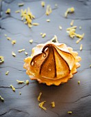 A lemon curd tartlet with a meringue topping on a grey surface surrounded by lemon zest
