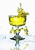 Gelbes Getränk spritzt aus dem Glas