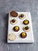 Crackers and pumpernickel topped with various spreads