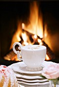 A cappuccino in front of an open fire
