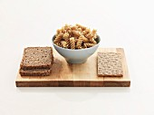Wholemeal bread, wholemeal pasta and wholemeal crispbread on a wooden board