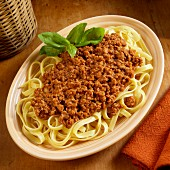 Fetuccini pasta with a meat sauce garnished with basil