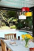 Ehemalige Backformen in verschiedenen Farben als Hängeleuchten über Terrassentisch, im Hintergrund Pool