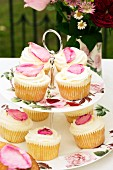 Rose petal cupcakes on the cake stand decorated with roses