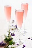 Drei rosafarbene Champagnercocktails
