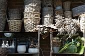 Im Regal gestapelte Weidenkörbe und Gefässe, an der Seite Wurzelgeflecht