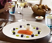 Smoked salmon with egg, caviar and purple potatoes on a table in a restaurant