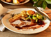 Christmas dinner with sliced turkey, vegetables and cranberries